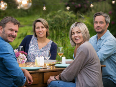 A summer evening of friends in their 40s gather around a table i